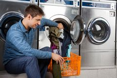 Man Putting Clothes In Washing Machine Stock Photo