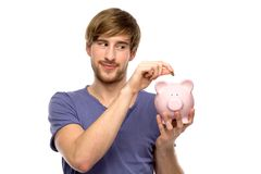 Man putting coin in piggy bank Royalty Free Stock Photography