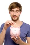Man putting coin in piggy bank Royalty Free Stock Photo