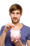 Man putting coin in piggy bank Stock Photo