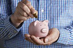 Man Putting Coin Into Piggy Bank Royalty Free Stock Photo