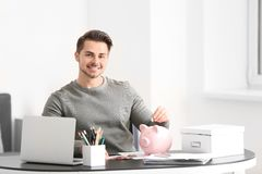 Man putting coin into piggy bank indoors. Money savings concept stock photo