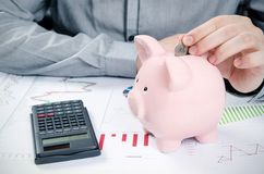 Man putting coin in piggy bank. Royalty Free Stock Photography