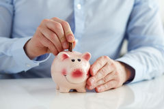 Man putting coin into piggy bank Stock Photography