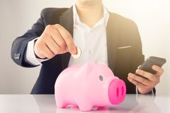 Man putting a coin into a pink piggy bank concept. For savings and finance Royalty Free Stock Image
