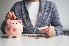 Man putting coin into small piggy bank. In the office royalty free stock images