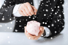 Man putting coin into small piggy bank Stock Image