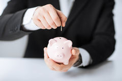Man putting coin into small piggy bank Royalty Free Stock Image