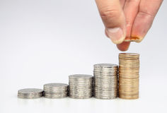 Man putting coin to rising stack of coins. Close-up of man putting coin to rising stack of coins stock photography
