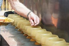 Man putting coins in monk`s alms bowl stock photography