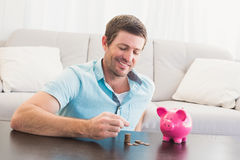 A man putting coins in piggy bank Royalty Free Stock Images