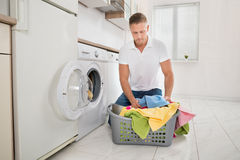 Man Putting Colorful Towels Into The Washing Machine Royalty Free Stock Photos