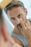 Man putting contact lenses in his eyes Stock Photo