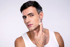 Man putting cream on a face stock photos