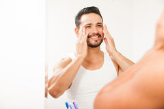 Man putting on cream on his face Stock Image