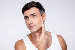 Man putting on cream lotion on face Stock Photography