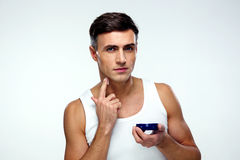 Man putting on cream lotion on face Royalty Free Stock Image