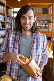 Man putting a croissant in paper bag Royalty Free Stock Photo