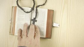 Bible above cross heart slow. A man putting a cross and a heart on a bible. View from above stock footage