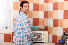 Man putting cup in microwave Royalty Free Stock Photography