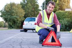 Man putting danger triangle sign after car breakdown Stock Photos