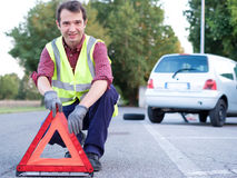 Man putting danger triangle sign after car breakdown Royalty Free Stock Photo