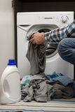 Man putting dirty clothes into washing machine Royalty Free Stock Photo
