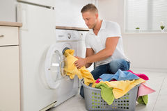 Man Putting Dirty Clothes Into The Washing Machine Royalty Free Stock Photos