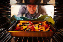 Man Putting Dish Of Vegetables Into Oven To Roast Royalty Free Stock Photos