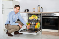 Man Putting Dishwasher Soap Tablet In Detergent Dishwasher Box Stock Photography