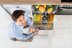 Man Putting Dishwasher Soap Tablet In Dishwasher Stock Image