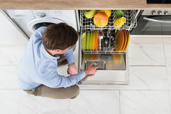 Man Putting Dishwasher Soap Tablet In Dishwasher Stock Photo