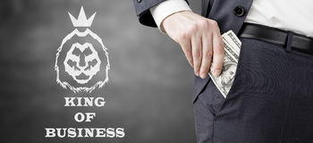 Man putting dollars into pockets. Close up of businessman putting several dollar bills into his pocket. King of business sketch is depicted beside him. Concept Stock Photo