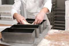 Man putting dough into metal form on table. In bakery Stock Images