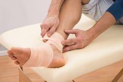 Man putting elastic bandage on foot Royalty Free Stock Image