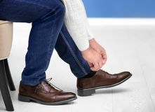 Man putting on elegant leather shoes indoors. Closeup Royalty Free Stock Images