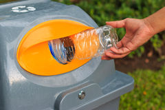 Man putting empty plastic bottle into public recycling bin. Stock Photos