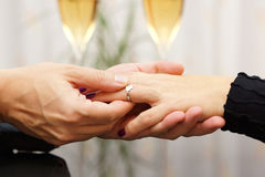 Man putting  engagement ring on the finger of his fiance Stock Photo