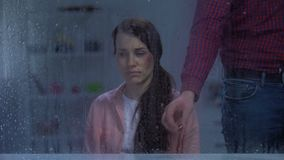 Man putting engagement ring in front of wife with wounded face, divorce, rain. Stock footage stock video