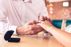 Man putting engagement ring on womans finger Royalty Free Stock Photos