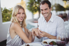 Man putting engagement ring on womans hand Royalty Free Stock Images