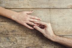 Man putting on an engagement to his woman. Royalty Free Stock Images