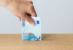 Man putting euro money into donation box Royalty Free Stock Photo