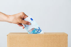 Man putting euro money into donation box. Charity, finances, funding, investment and people concept - male hand putting euro money into donation box Stock Photo