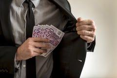 Man putting euros inside his jacket pocket Stock Photo