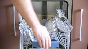 Man is putting a few plates into a dishwasher. stock video