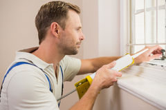 Man putting filling between window and wall Stock Image