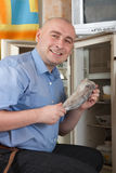 Man putting  fish into refrigerator Stock Photos