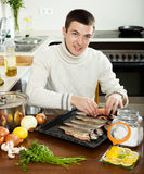Man putting   fish into sheet pan Stock Photography