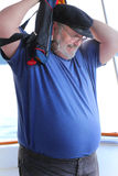 Man putting on floatations device. A closeup of an older scruffy man wearing a wool captain's bill cap and glasses putting on a floatations device or life jacket Royalty Free Stock Image
